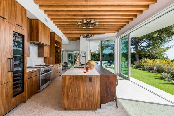 The customized walnut kitchen opens to the outdoors and features leathered Perla Venata Quartzite countertops and Miele appliances.
