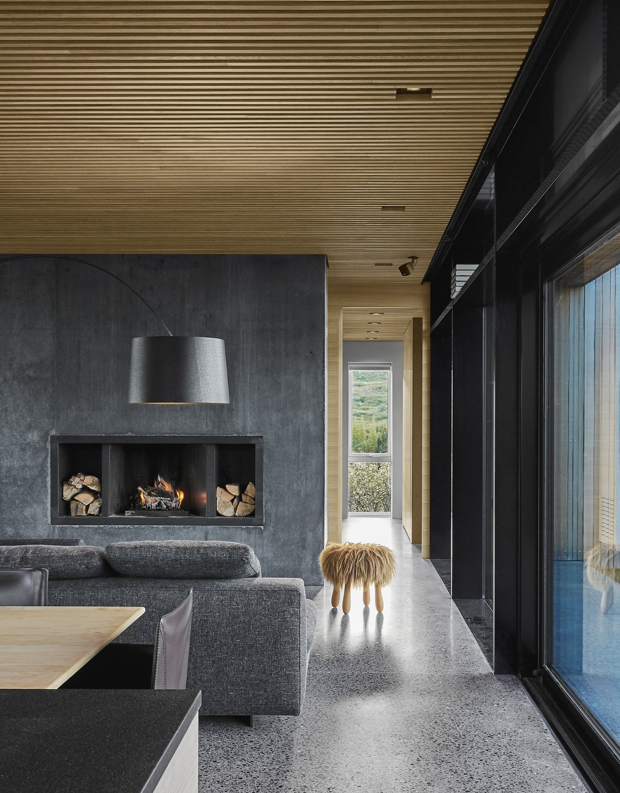 Living Room, Standard Layout Fireplace, Sectional, Chair, Wood Burning Fireplace, Table, Stools, Concrete Floor, Recessed Lighting, and Floor Lighting The minimalist material palette is picked up on the interiors as well, where a black concrete fireplace plays off the polished aggregate concrete floors.   Best Photos from A Timber-and-Concrete Summer House in Iceland Boasts Breathtaking Views