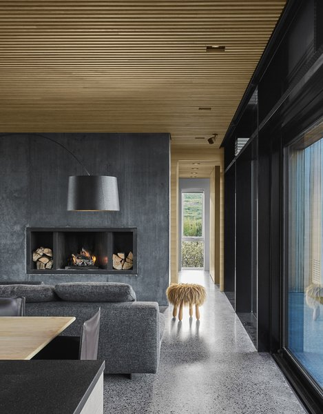 The minimalist material palette is picked up on the interiors as well, where a black concrete fireplace plays off the polished aggregate concrete floors.