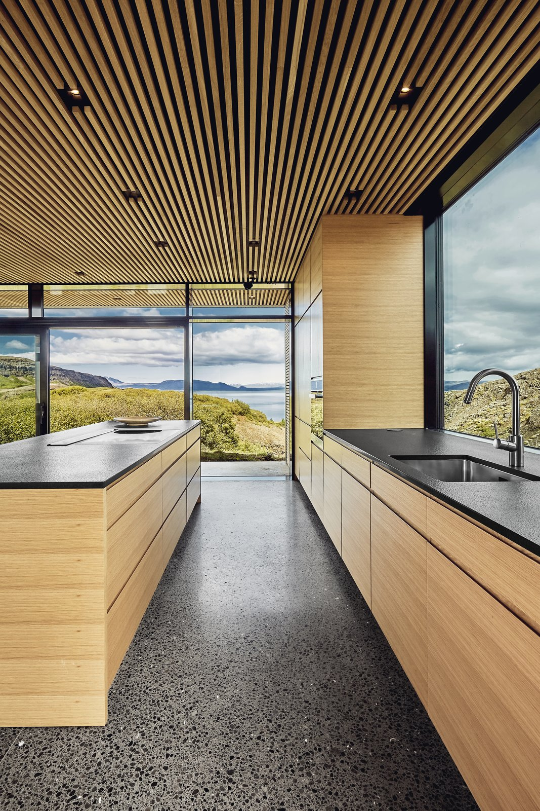 Kitchen, Undermount Sink, Recessed Lighting, Wood Cabinet, Wall Oven, Cooktops, and Concrete Floor The view is framed from every angle.  Best Photos from A Timber-and-Concrete Summer House in Iceland Boasts Breathtaking Views