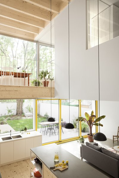 A study area on the mezzanine level overlooks the kitchen. Extensive glazing gives the ground floor living spaces a direct visual link with the courtyard and terrace.