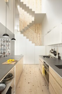 The kitchen faces the back garden and benefits from a double height atrium space. Pine has been used for the kitchen flooring and cabinets, a design element that is also picked up in the stairwell. The built-in refrigerator and pantry are cleverly hidden under the first flight of stairs.