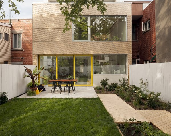 Although the home's historic front facade needed to be preserved, the back of the residence was ripe for a remodel. The architects cladded the exterior in eastern cedar. The wood is offset with large expanses of glass, as well as yellow accents to add a playful atmosphere.