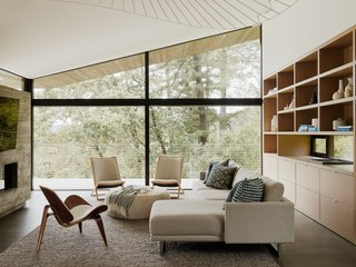 Large picture windows in the open living room frame the surrounding forest.
