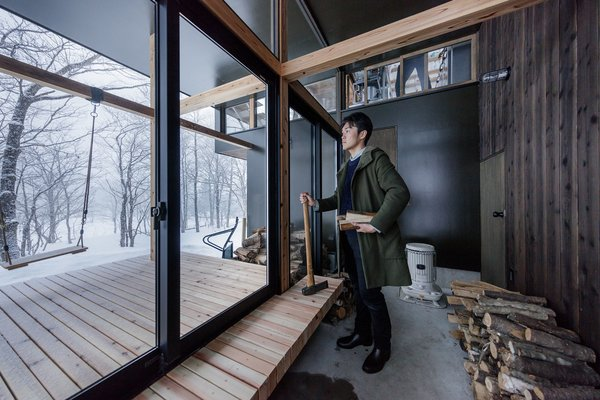 The indoor portion is set behind sliding glass doors and can be used for storing firewood.
