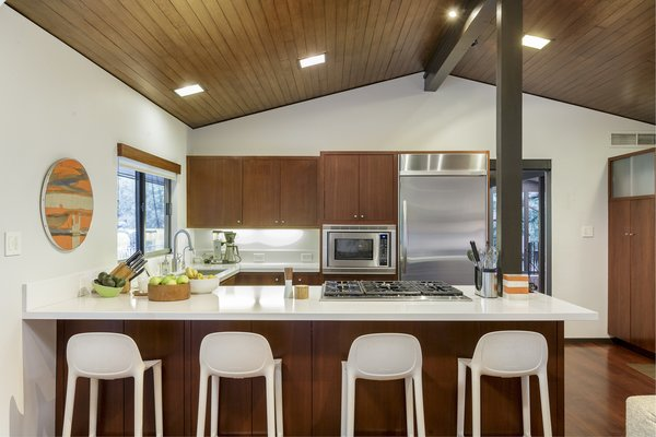 The open kitchen boasts stainless steel appliances and warm wood cabinetry.