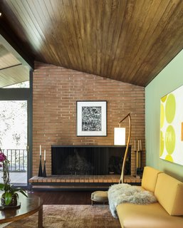 A brick, wood-burning fireplace anchors the area.