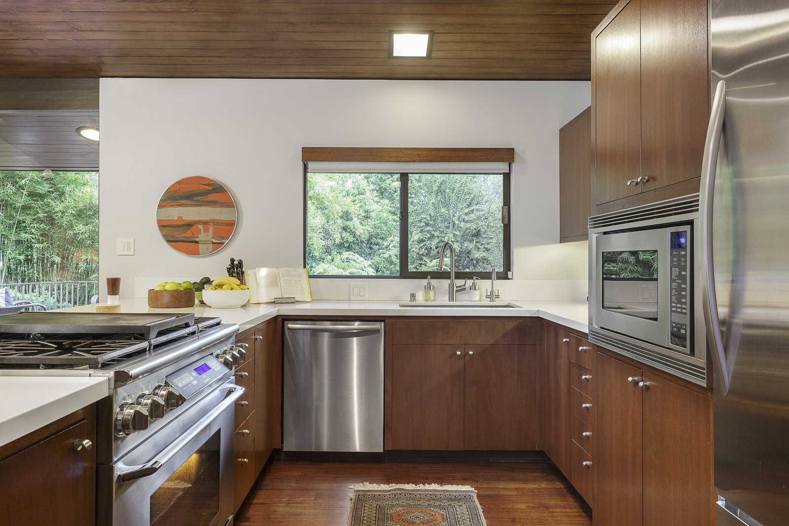 Kitchen, Ceiling Lighting, Range, Refrigerator, Wood Cabinet, Dark Hardwood Floor, Undermount Sink, Recessed Lighting, Dishwasher, and Microwave The kitchen also has direct access to the outdoor deck and a deluxe barbeque station.  Photo 7 of 17 in A Southern Californian Midcentury With Japanese Influences Asks $3.13M