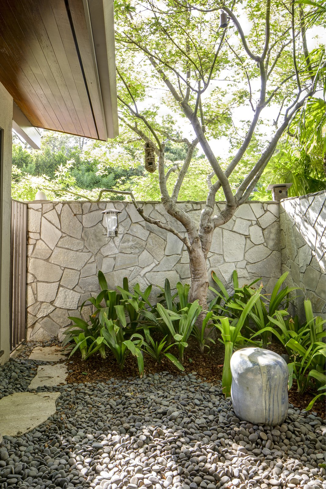 Outdoor, Horizontal Fences, Wall, Gardens, Side Yard, Stone Fences, Wall, and Trees The bedroom wing also offers access to a private courtyard.  Photo 16 of 17 in A Southern Californian Midcentury With Japanese Influences Asks $3.13M