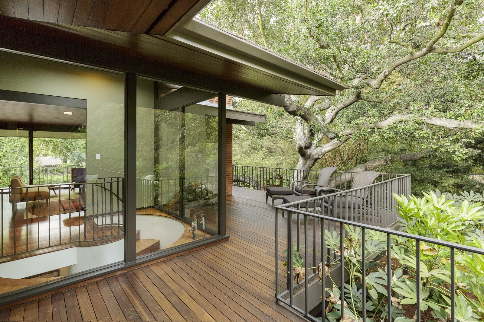 Outdoor, Trees, Large Patio, Porch, Deck, Side Yard, and Wood Patio, Porch, Deck The wraparound deck enhances the homes' indoor/outdoor lifestyle.  Photo 10 of 17 in A Southern Californian Midcentury With Japanese Influences Asks $3.13M