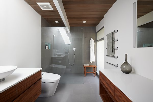"Bathroom updates also maintain the bright and airy feel of the rest of the home. The flooring is a large porcelain tile (24"" x 24"") in a neutral gray tone, serving as a uniform background against which the other materials can stand out."