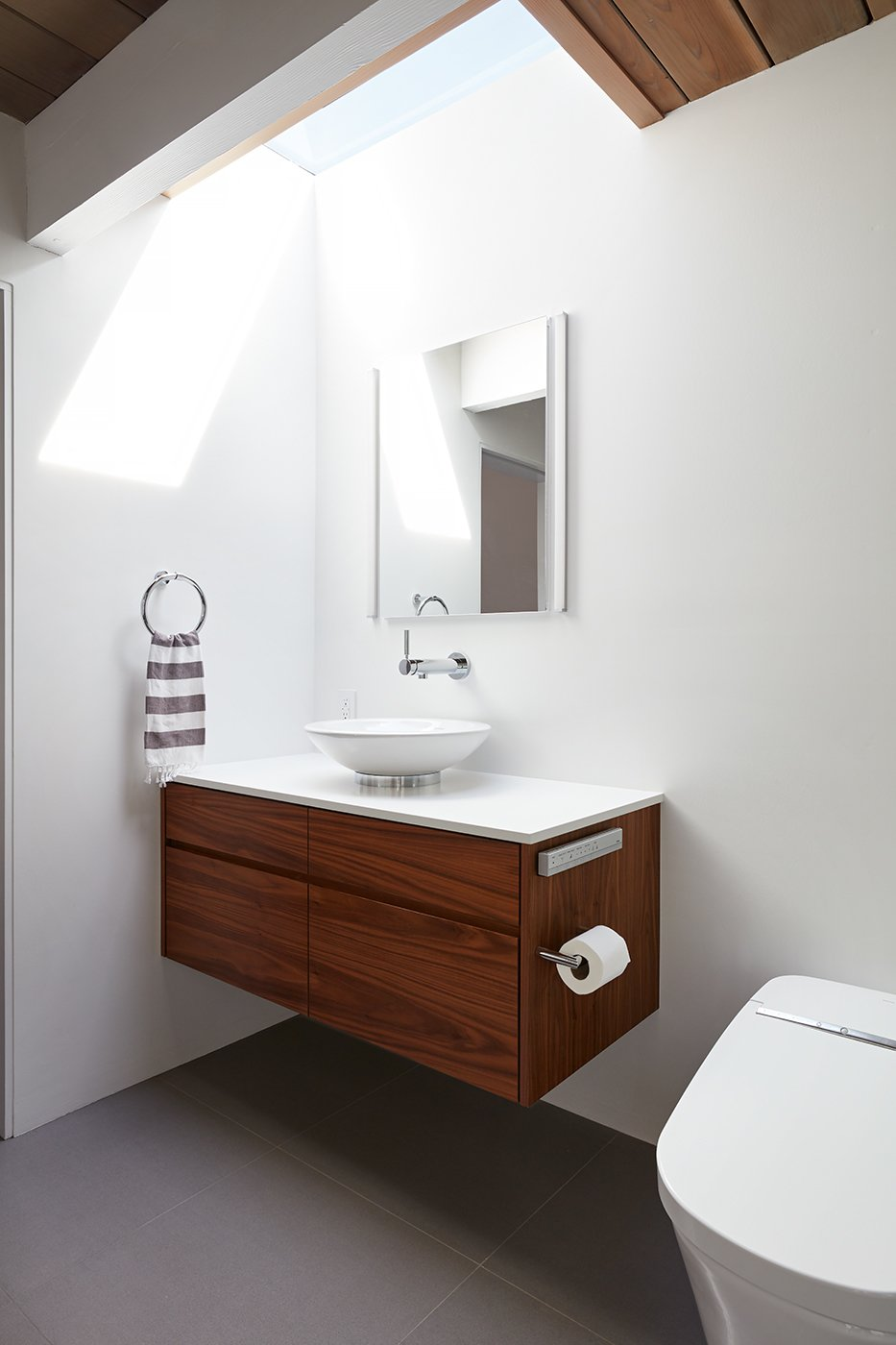 Bath Room, One Piece Toilet, Porcelain Tile Floor, Engineered Quartz Counter, and Vessel Sink A bathroom skylight increases the sense of space.     Photo 13 of 14 in This Eichler Home in California Mixes Scandinavian Vibes With Midcentury Charm