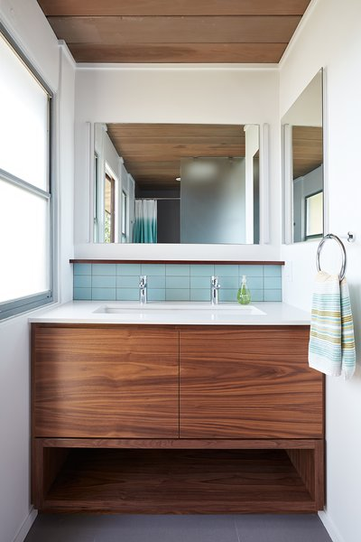 Walnut has also added warmth and contrast to the bathroom vanities. While the Heath Classic Field ceramic tile in Modern Blue has been used sparingly throughout the home, it still adds color to the hall bath vanity backsplash and at the shampoo niches in both bathrooms.