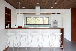 Kitchen cabinetry, countertops, appliances, and light fixtures are all white, making the kitchen feel more light and airy. The pale blue backsplash matches the shade of the Heath tiles that is in the bathroom.