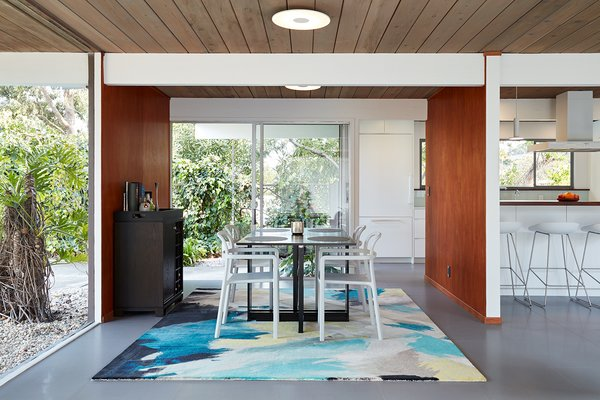 Some of this Eichler's original highlights remain, such as the tongue-and-groove redwood ceiling decking and the now re-stained luan wall paneling. In the kitchen, walnut is juxtaposed with crisp white, and the light blue found in the dining area is a unifying accent color.