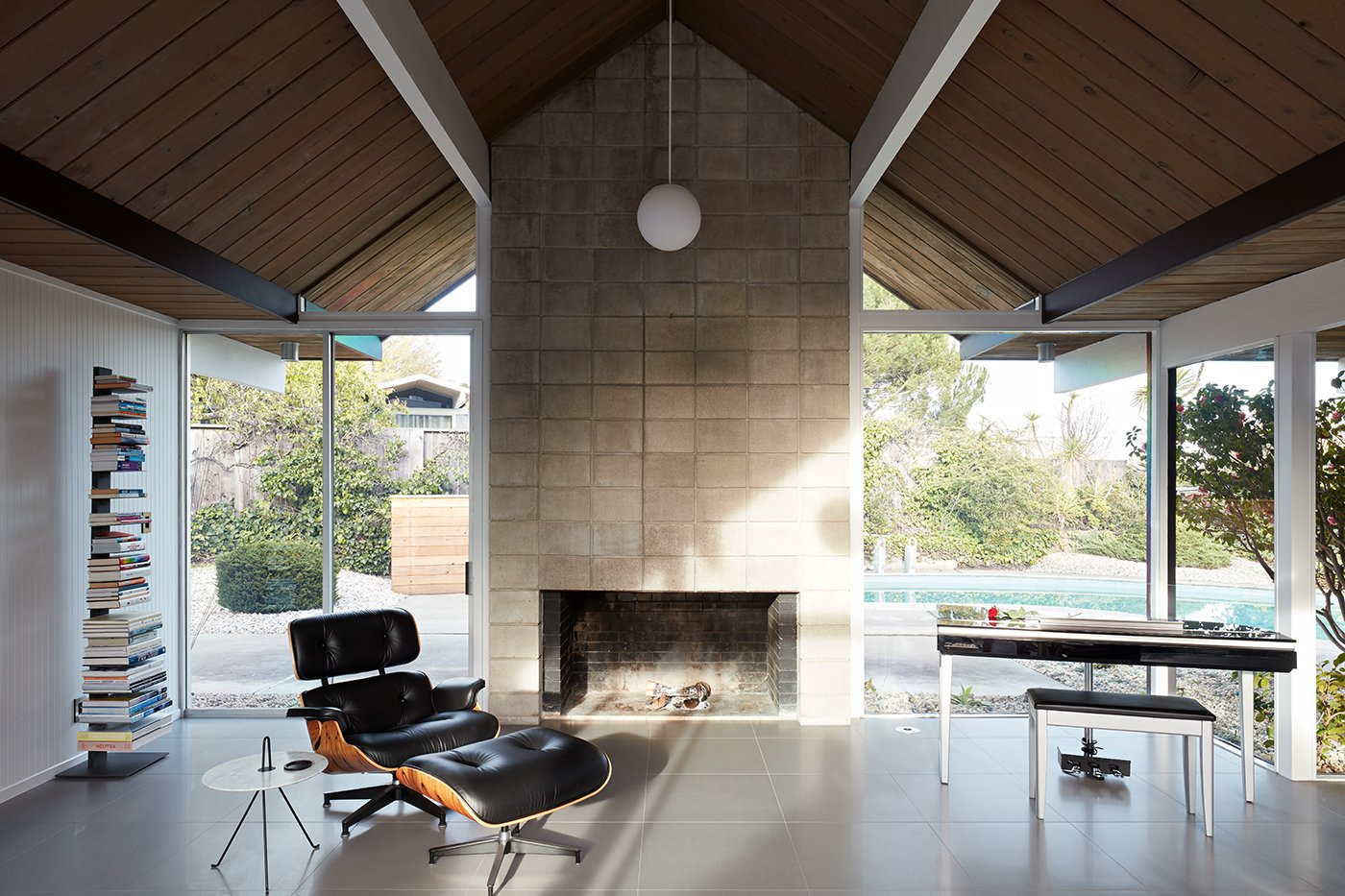 Living Room, Chair, End Tables, Wood Burning Fireplace, Recliner, Pendant Lighting, Standard Layout Fireplace, and Ottomans Another original Eichler element which the homeowners have chosen to keep is the concrete masonry fireplace.    Photo 9 of 14 in This Eichler Home in California Mixes Scandinavian Vibes With Midcentury Charm
