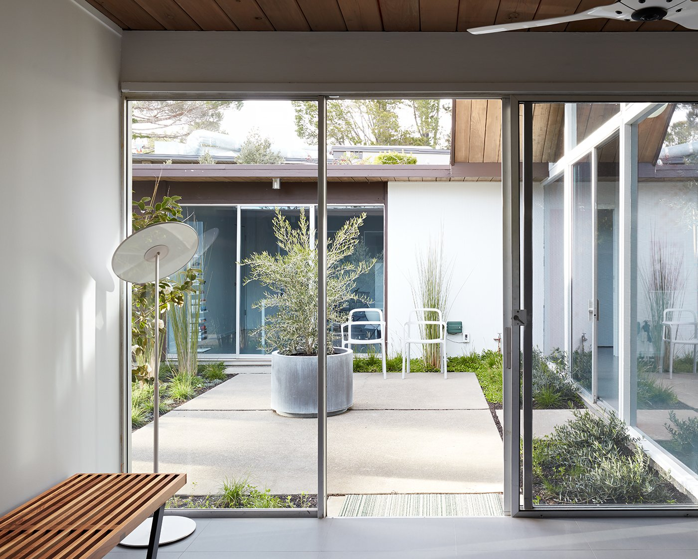 Outdoor, Garden, Shrubs, Grass, Small Patio, Porch, Deck, and Walkways The goal of the remodel was to preserve the home's classic look, while also updating it.     Photo 2 of 14 in This Eichler Home in California Mixes Scandinavian Vibes With Midcentury Charm