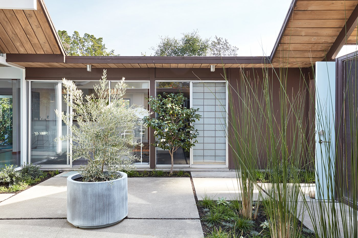 Exterior, Wood Siding Material, Mid-Century Building Type, House Building Type, and Flat RoofLine The atrium door at the front entry (on the right) is painted a light blue—the same accent color that has been used in the home's kitchen and bathroom.     Photo 1 of 14 in This Eichler Home in California Mixes Scandinavian Vibes With Midcentury Charm