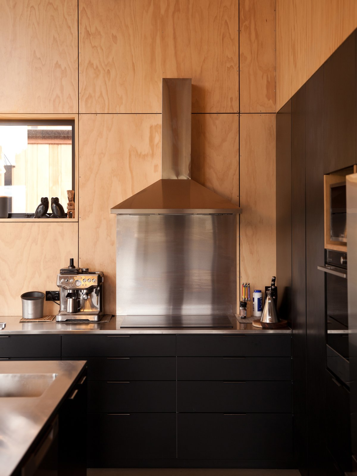 Kitchen, Metal Counter, Metal Backsplashe, Cooktops, Range Hood, Drop In Sink, Wall Oven, and Wood Backsplashe The kitchen is both stylish and practical.  Photos from A Tiny Cabin Boasts Big Views of the New Zealand Countryside