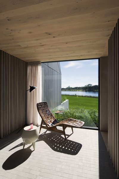 A quiet spot for contemplation takes advantage of the surrounding scenery. Cedar screens provide privacy and filter light, while also picking up on the lines of the exterior vertical siding.