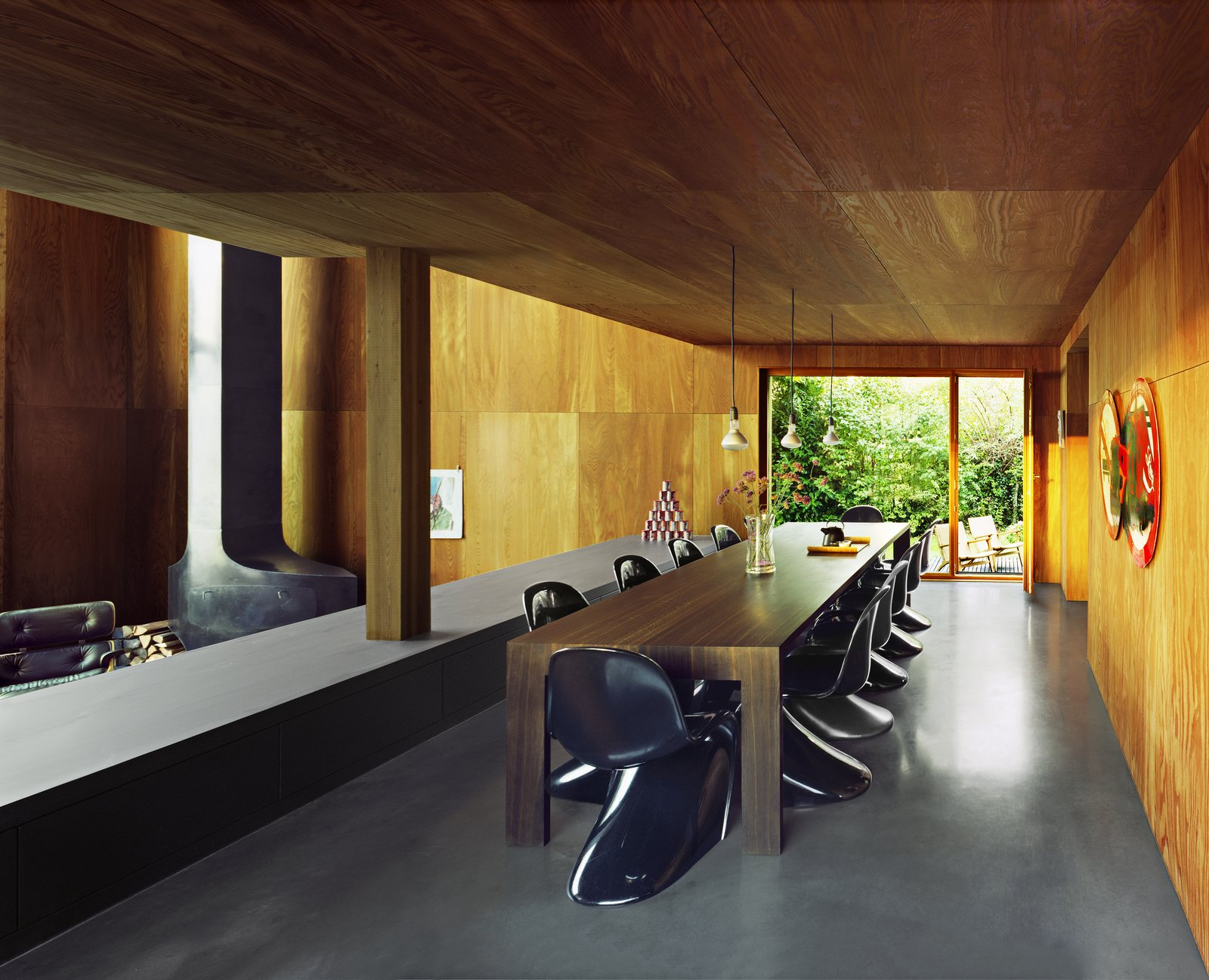 Dining Room, Table, Wood Burning Fireplace, Concrete Floor, Chair, and Pendant Lighting The spacious dining area overlooks the open living room and the surrounding greenery.  Photo 6 of 13 in A Sculptural Steel Abode on Lake Geneva Is Up For Auction