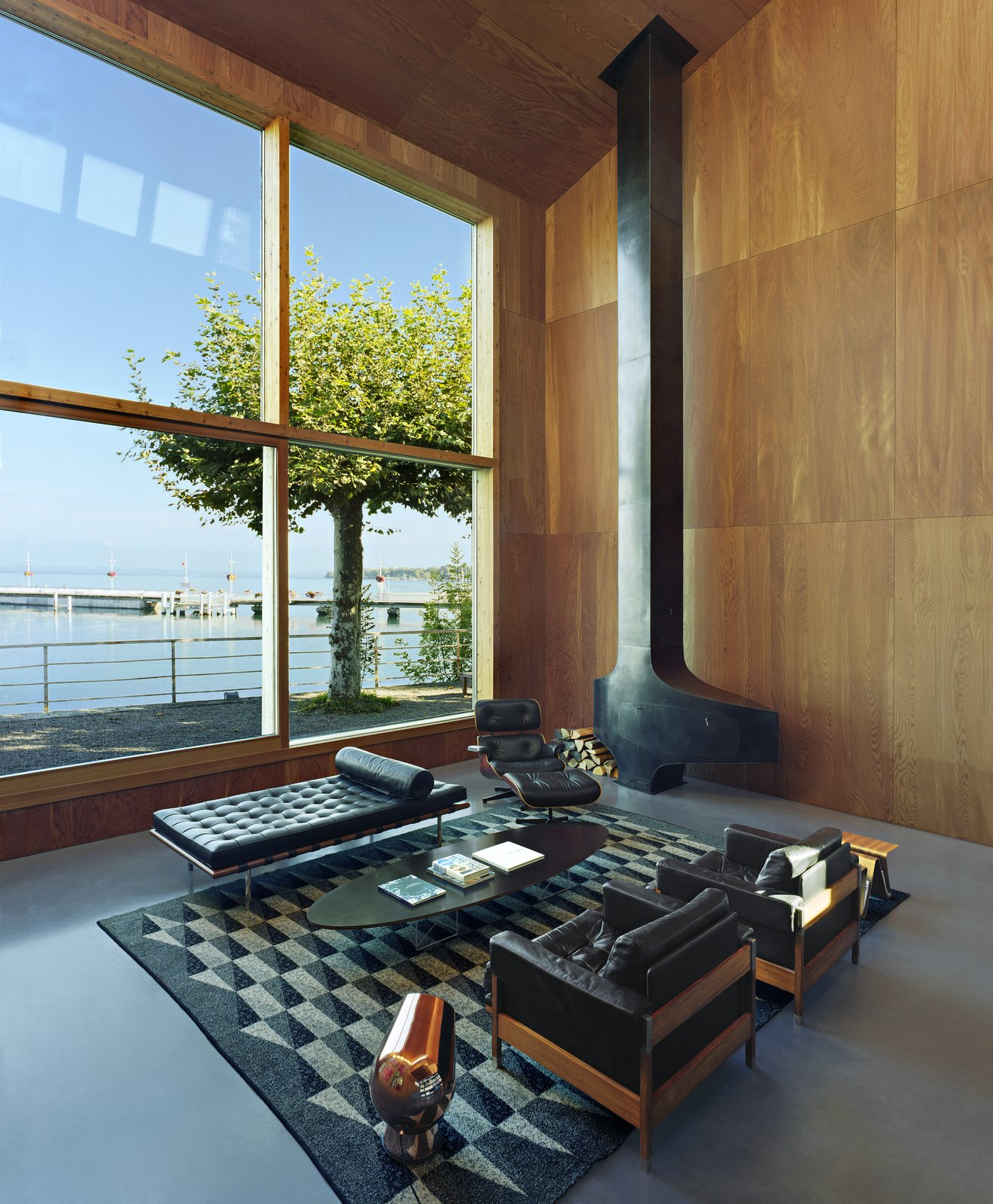 Living Room, Wood Burning Fireplace, Recliner, Coffee Tables, Chair, Concrete Floor, Bench, Rug Floor, and Ottomans A wall of windows frames the spectacular view of the lake and imparts a dynamic sense of place throughout the open-plan living area.   Photo 4 of 13 in A Sculptural Steel Abode on Lake Geneva Is Up For Auction