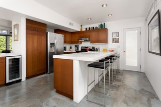 The kitchen features many upgrades, including new cabinetry, quartz countertops, stainless steel appliances, a wine fridge, and a breakfast bar.