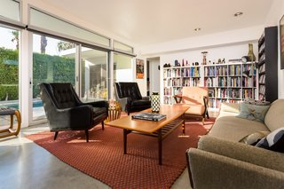 The open-plan living room has a wall of glass sliding doors and clerestory windows that trace the iconic angled roofline.