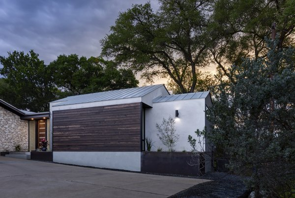 The wood and stucco addition features a pitched metal roof that complements the existing home's midcentury style. The hidden side windows (by the planter) allow natural light to filter in.