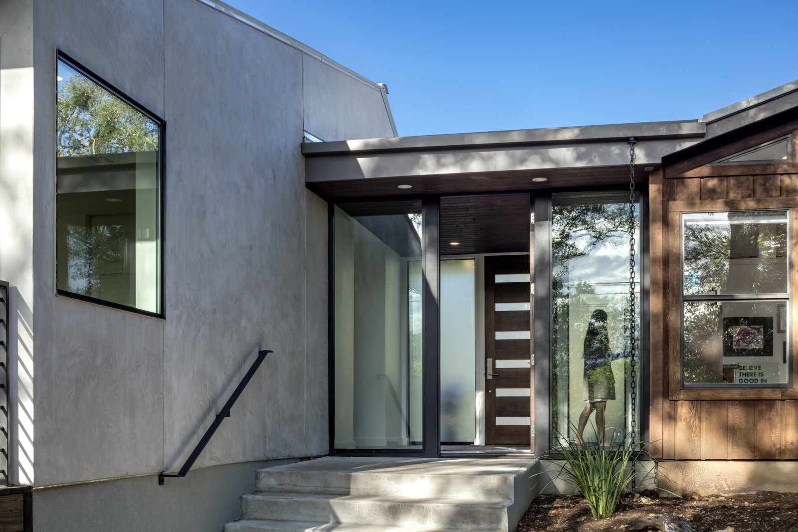 Doors, Wood, Swing, and Exterior A glass entry connects the addition and offers a clear view of—and direct access to–the natural landscape surrounding the site.     Best Doors Wood Exterior Photos from An Austin Midcentury Welcomes a Discreet Home Office Addition