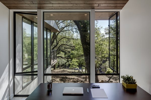 Unlike its solid front, the back of Creekbluff Studio opens to the outdoors with large windows, floor-to-ceiling glass doors, and a patio tucked between tree canopies which overlook the nearby creek.