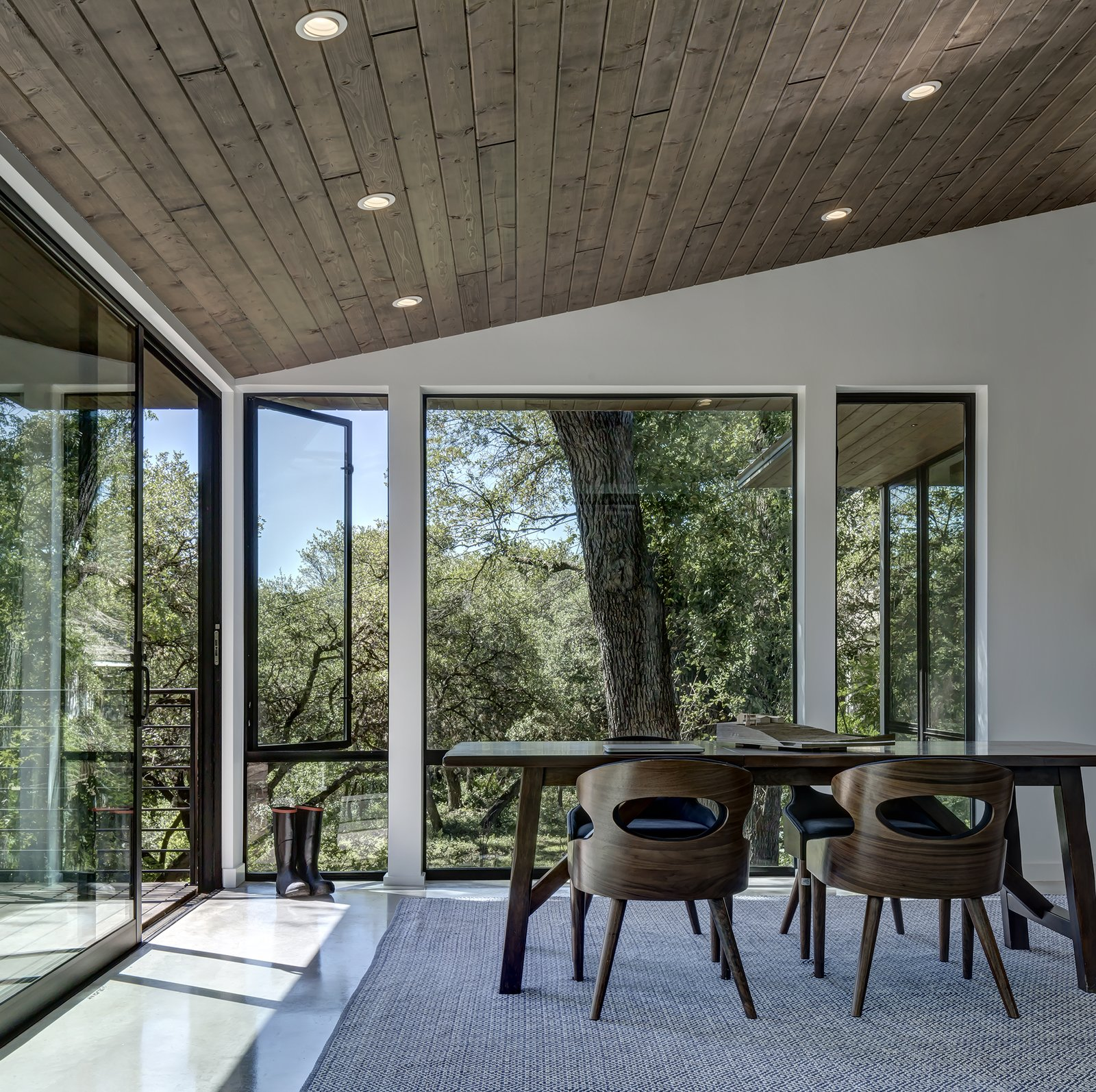 Office, Chair, Desk, Concrete, and Rug Unlike the solid front facade, the back elevation is replete with glazing.  Best Office Desk Concrete Photos from An Austin Midcentury Welcomes a Discreet Home Office Addition