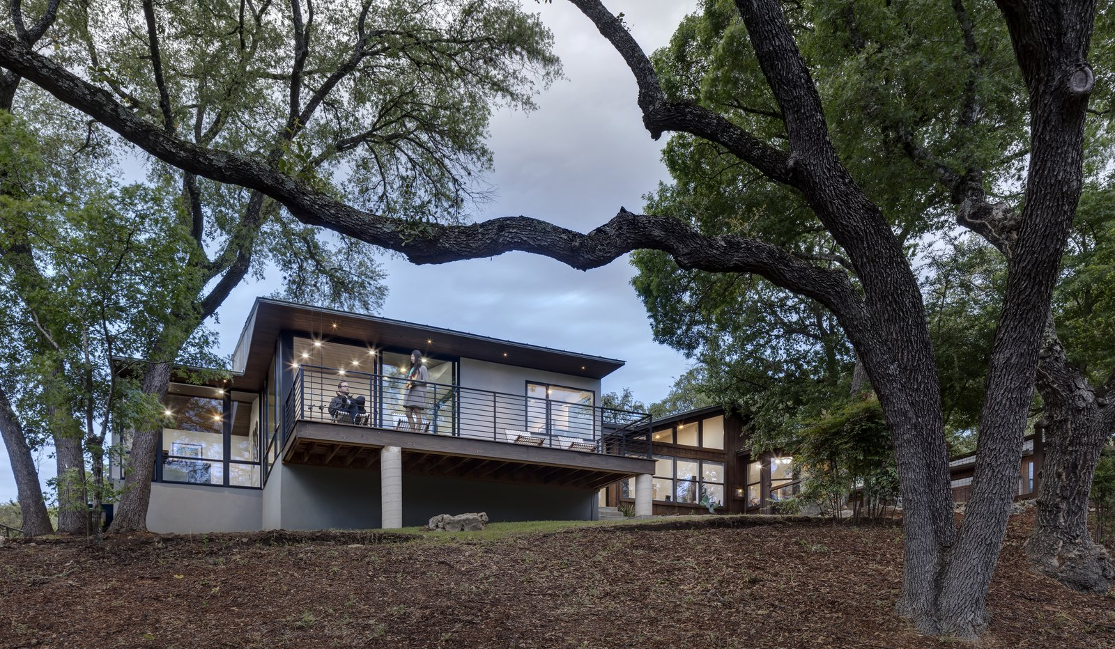 Exterior, Wood, House, Glass, Gable, Concrete, Metal, and Mid-Century The back deck provides the perfect spot for entertaining and enjoying the lush landscape.     Best Exterior Metal Wood Gable Concrete Photos from An Austin Midcentury Welcomes a Discreet Home Office Addition
