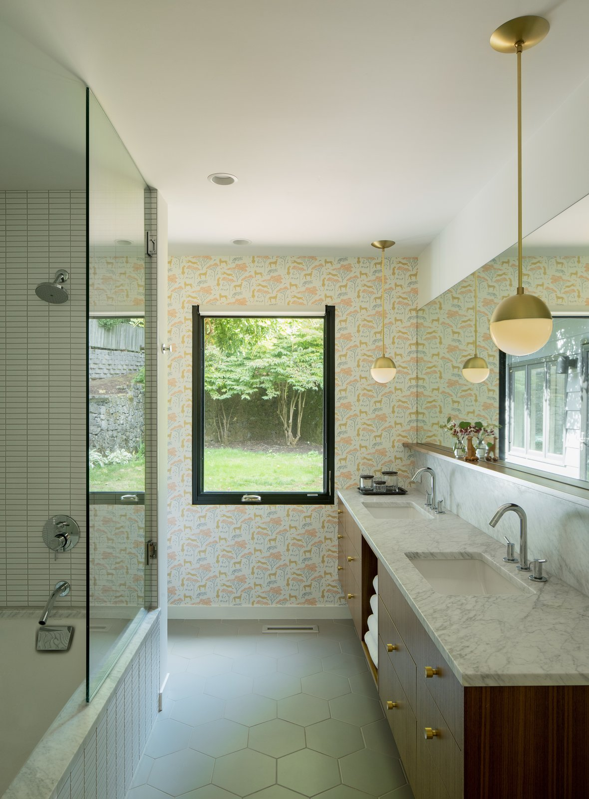 Bath, Porcelain Tile, Pendant, Marble, Undermount, Open, Undermount, Recessed, and Full Now, the space looks both sophisticated and playful thanks to the addition of whimsical animal-printed wallpaper, marble countertops, tiles from Ann Sacks, and brass pendant lights designed by Cedar & Moss for Rejuvenation.    Best Bath Marble Undermount Recessed Undermount Photos from Before & After: A 1950s Midcentury Abode Gets a Gorgeous Upgrade