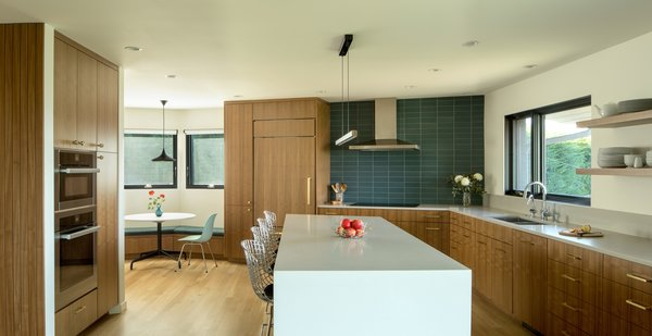 The team expanded the kitchen and gave it a modern look that now features stunning walnut cabinets, gray Caesarstone counters, and a beautiful teal backsplash with tile from the Ann Sacks Modern Line.