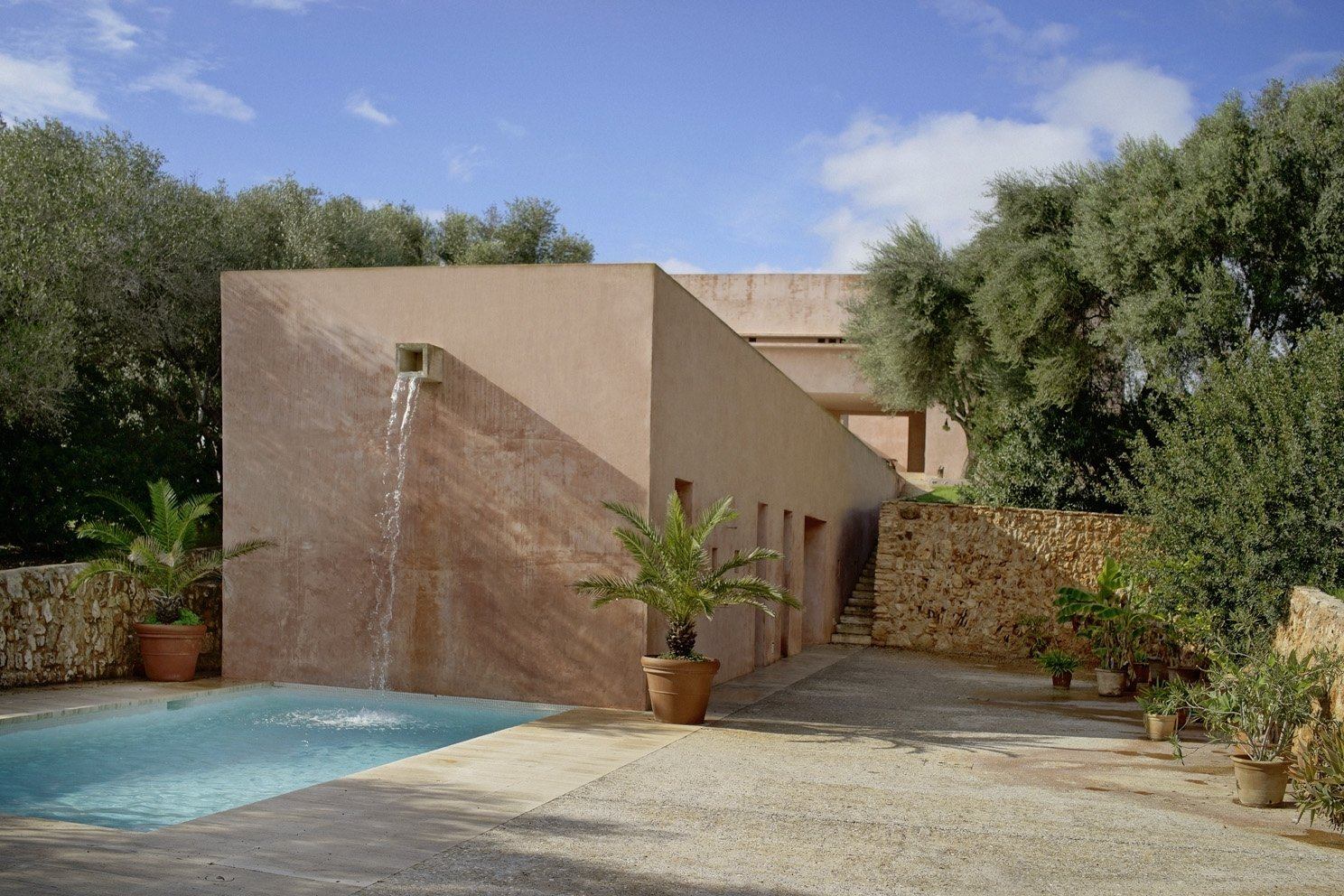 Outdoor, Stone, Shrubs, Small, Large, Side Yard, and Trees Amenities include a pool with a waterfall and a sunken tennis court.     Best Outdoor Shrubs Small Photos from This John Pawson-Designed Retreat in Mallorca Is a Minimalist's Dream
