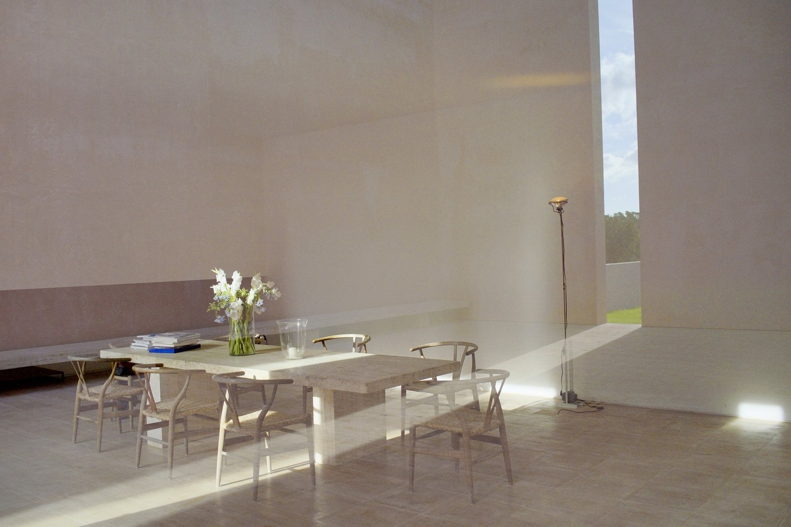 Dining Room, Chair, Table, and Floor Lighting The use of cut-outs is a constant theme that runs throughout the property, which provides the interior spaces with dramatic lighting.    Photo 8 of 11 in This John Pawson-Designed Retreat in Mallorca Is a Minimalist's Dream
