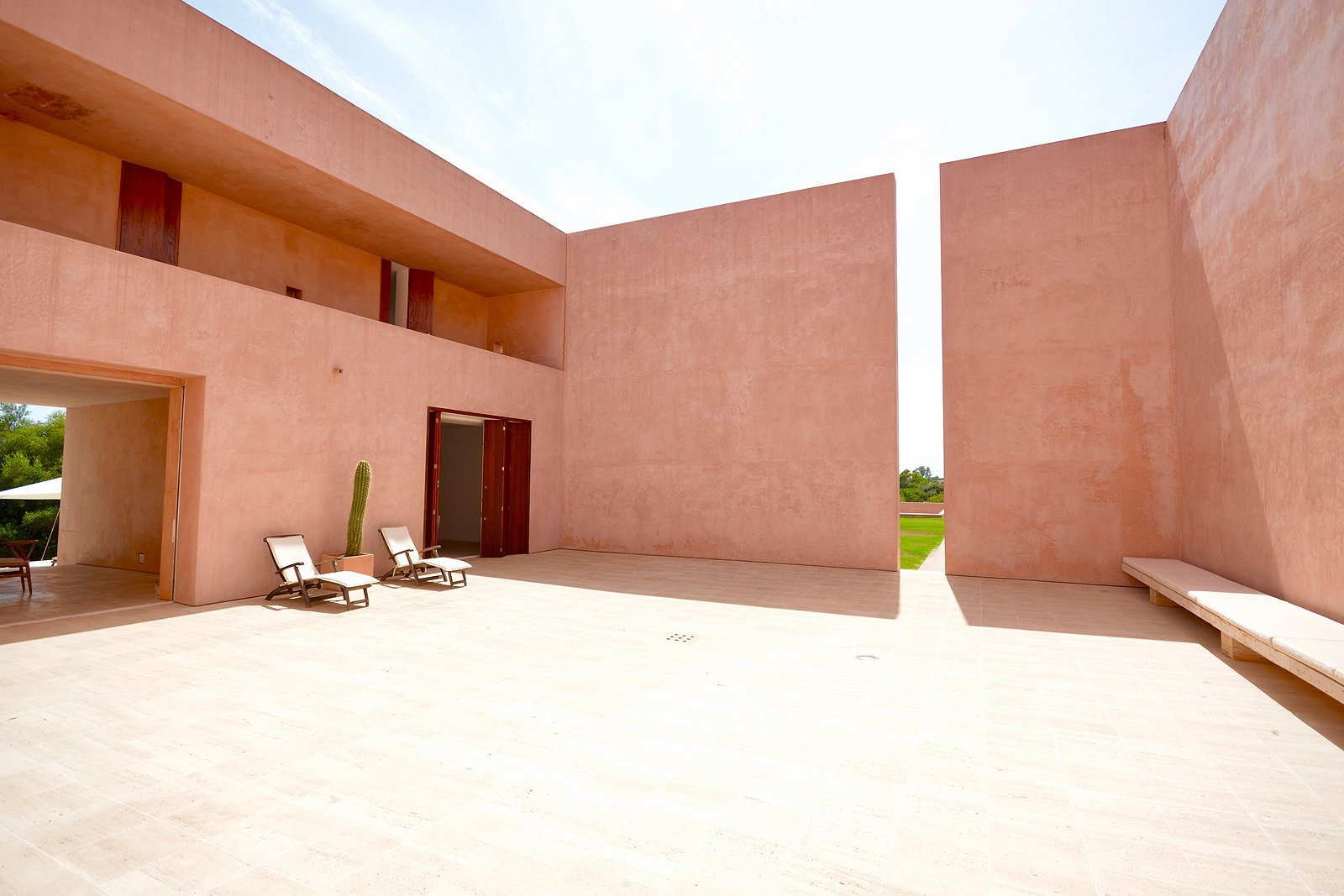 Outdoor, Large Patio, Porch, Deck, and Side Yard The home has been built around a central courtyard, with the surrounding exterior wall featuring a dramatic cut-out that inserts both light and shadows into the design.    Photo 3 of 11 in This John Pawson-Designed Retreat in Mallorca Is a Minimalist's Dream