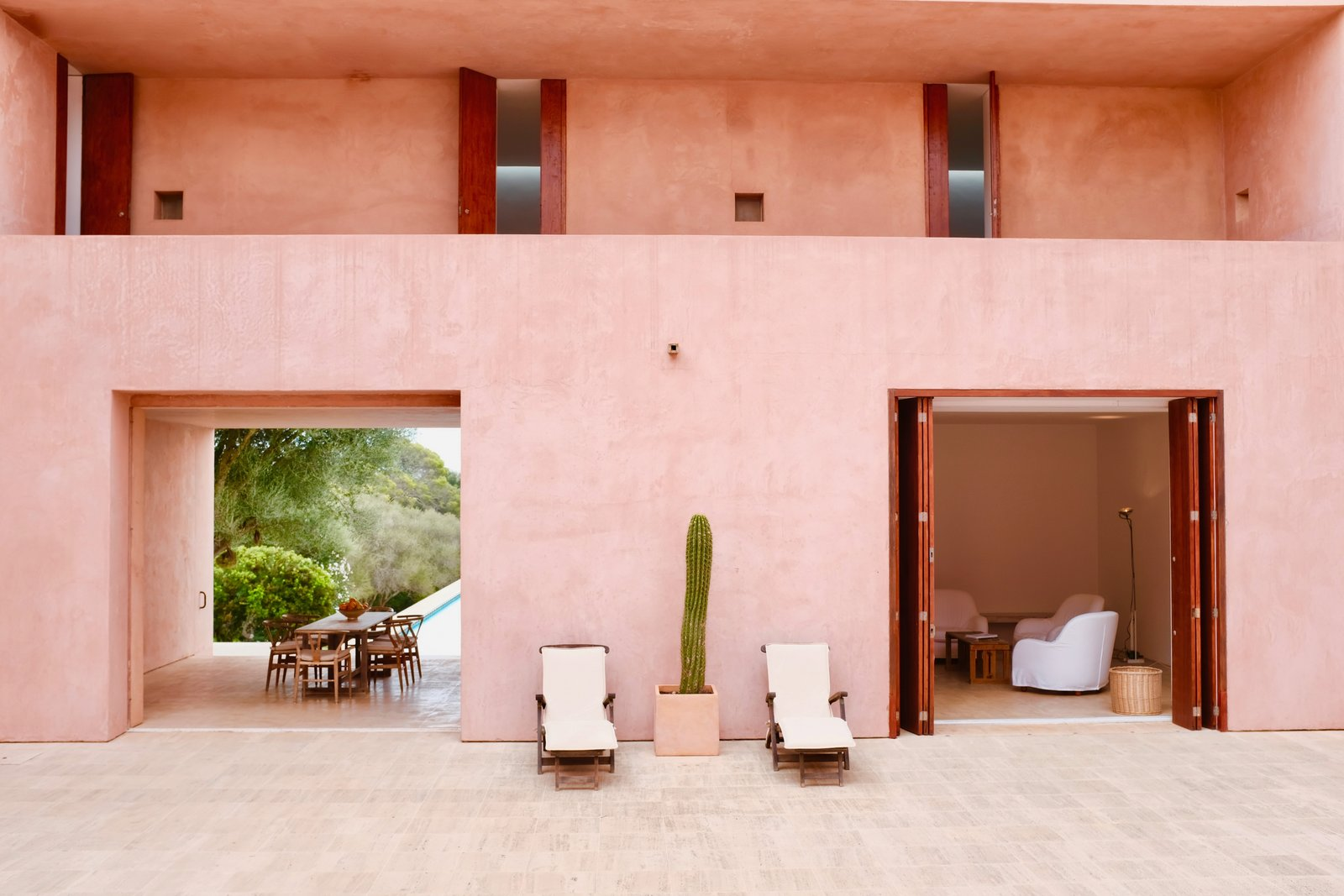 Outdoor, Side Yard, and Large Patio, Porch, Deck This Mallorcan villa was the firm's first full architectural project. It was originally built for German art dealers whom Pawson had met by chance on an Italian beach. Acclaimed for his moody minimalism, the architect lends his signature touch to this five-bedroom home. To obtain a rosy hue, pigments from the local red soil were mixed with plaster.    Photo 2 of 11 in This John Pawson-Designed Retreat in Mallorca Is a Minimalist's Dream from 12 Mediterranean Homes That Are the Antidote to Mid-Winter Blues