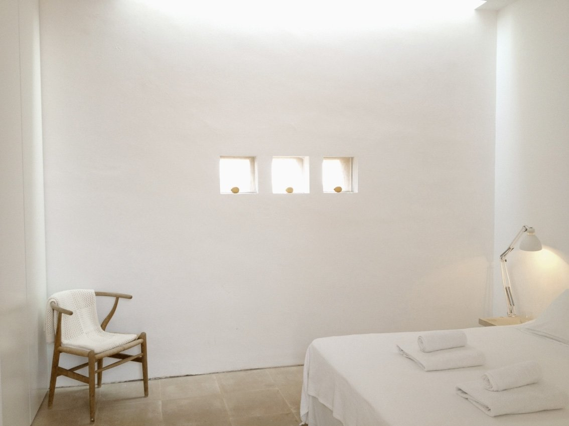Bedroom, Table Lighting, Chair, Bed, and Night Stands The minimalist interiors are predominantly white with an understated luxe vibe.     Photo 9 of 11 in This John Pawson-Designed Retreat in Mallorca Is a Minimalist's Dream