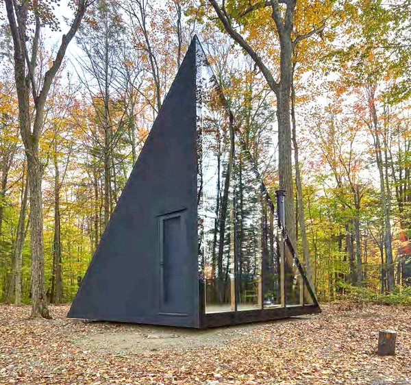 Inspired by the classic A-frame cabin design, architecture firm Bjarke Ingels Group (BIG) has created their first tiny home with Klein, a prefab-housing startup in New York. Sited in Hudson Valley, the 180-square-foot sleek black cabin is known as A45. Despite its small size, the cabin's innovative design creates more usable floor space by rotating the classic A-frame structure 45 degrees. This allows the lower part of the house to only touch on two corners, which maximizes the wall height to a soaring 13 feet inside. The resulting crystal-like shape gives A45 an ever-changing appearance.