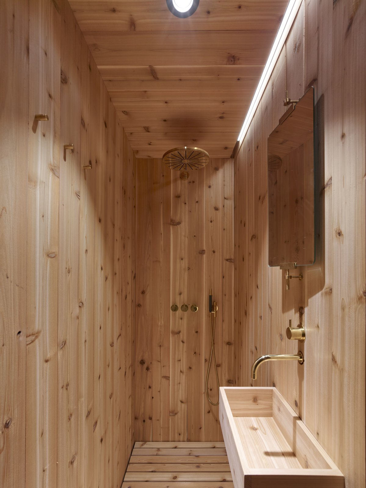 Bath Room, Open Shower, Drop In Sink, Wood Counter, Light Hardwood Floor, and Recessed Lighting The sauna-like bathroom is made of cedar and features fixtures from VOLA.    Best Photos from This Sleek, Angular Tiny Home Is Not Your Average A-Frame Cabin