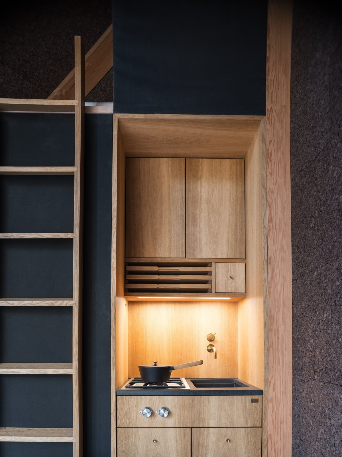 Kitchen, Wood Counter, Wood Backsplashe, Wood Cabinet, Cooktops, Undermount Sink, and Accent Lighting The A45 is outfitted with a petite kitchen designed by Københavns Møbelsnedkeri.     Photos from This Sleek, Angular Tiny Home Is Not Your Average A-Frame Cabin