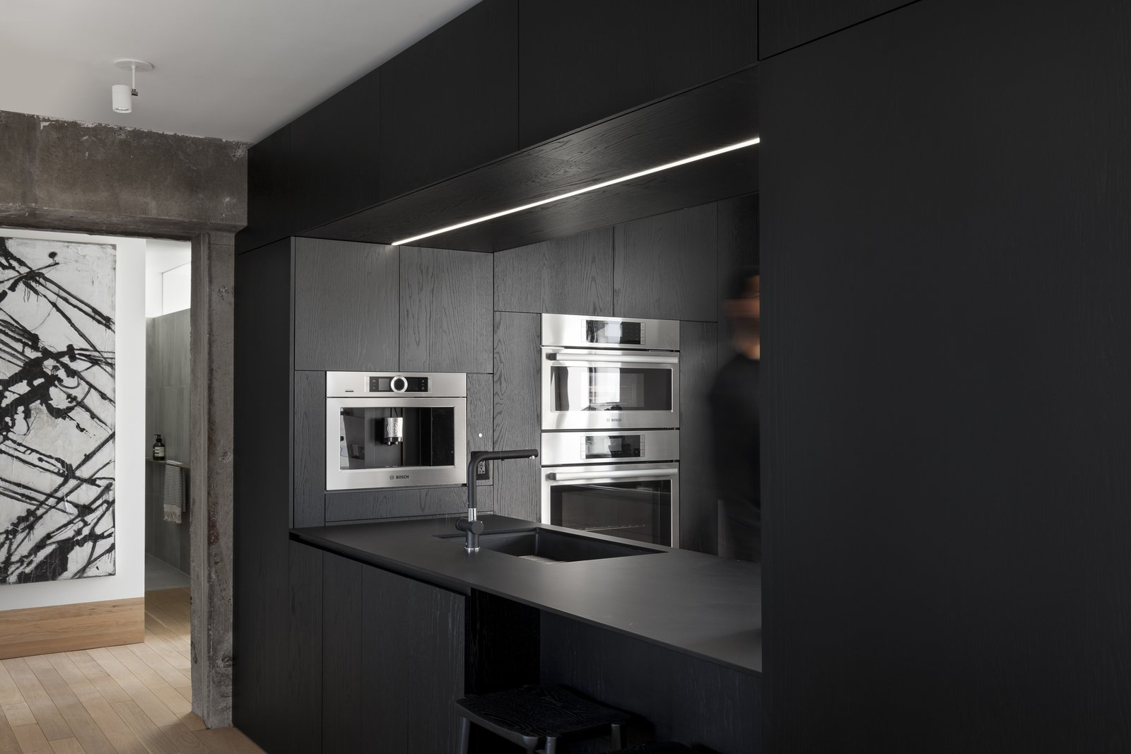 Kitchen, Ceiling, Wall Oven, Microwave, Undermount, and Light Hardwood The efficiently designed kitchen has been crafted by local kitchen brand À Hauteur d'homme.     Best Kitchen Microwave Ceiling Light Hardwood Undermount Wall Oven Photos from An Iconic T-Shaped Apartment Receives a Modern Makeover