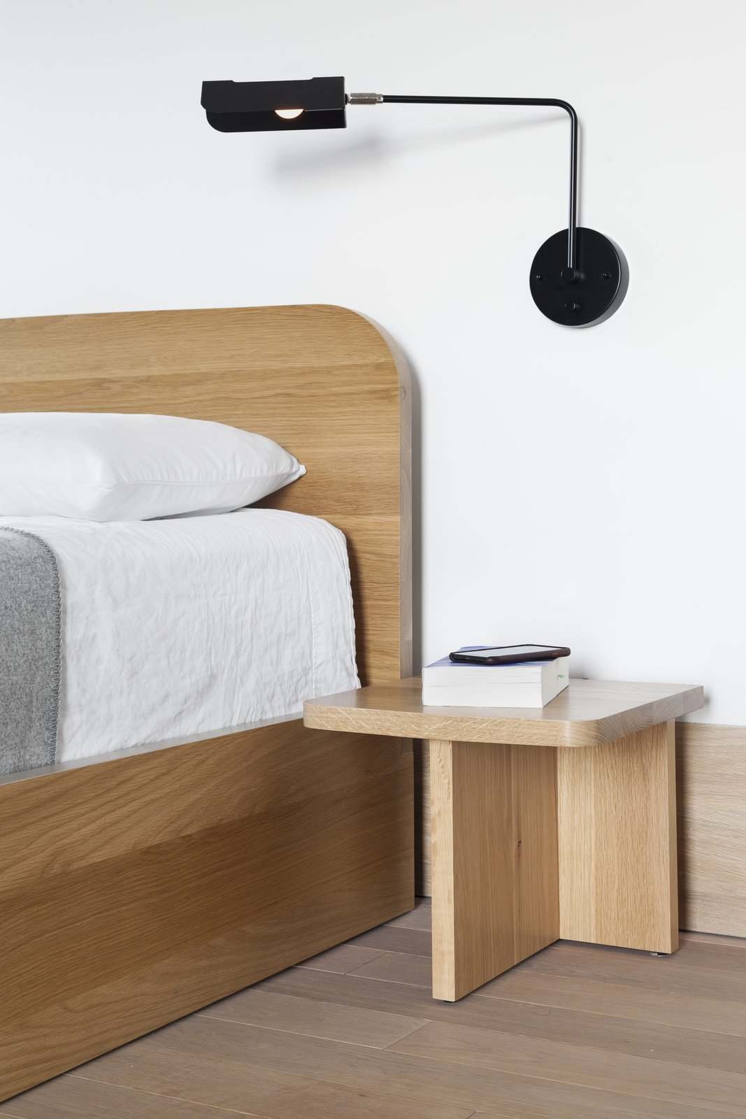Bedroom, Bed, Light Hardwood, Wall, and Night Stands A close-up of the nightstand and another piece from Sangaré's UNITÉ lighting collection.     Best Bedroom Night Stands Wall Photos from An Iconic T-Shaped Apartment Receives a Modern Makeover