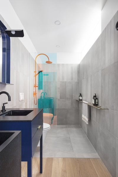 The bathrooms are a break from the minimalist aesthetic of the living spaces, injecting color and interesting finishes that include the use of a dichroic glass shower divider.