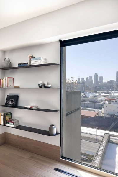 The window in the living room is framed by built-in shelves. The owners are collectors of local craft and design, and had ventilation grids custom-made specifically for the renovation.