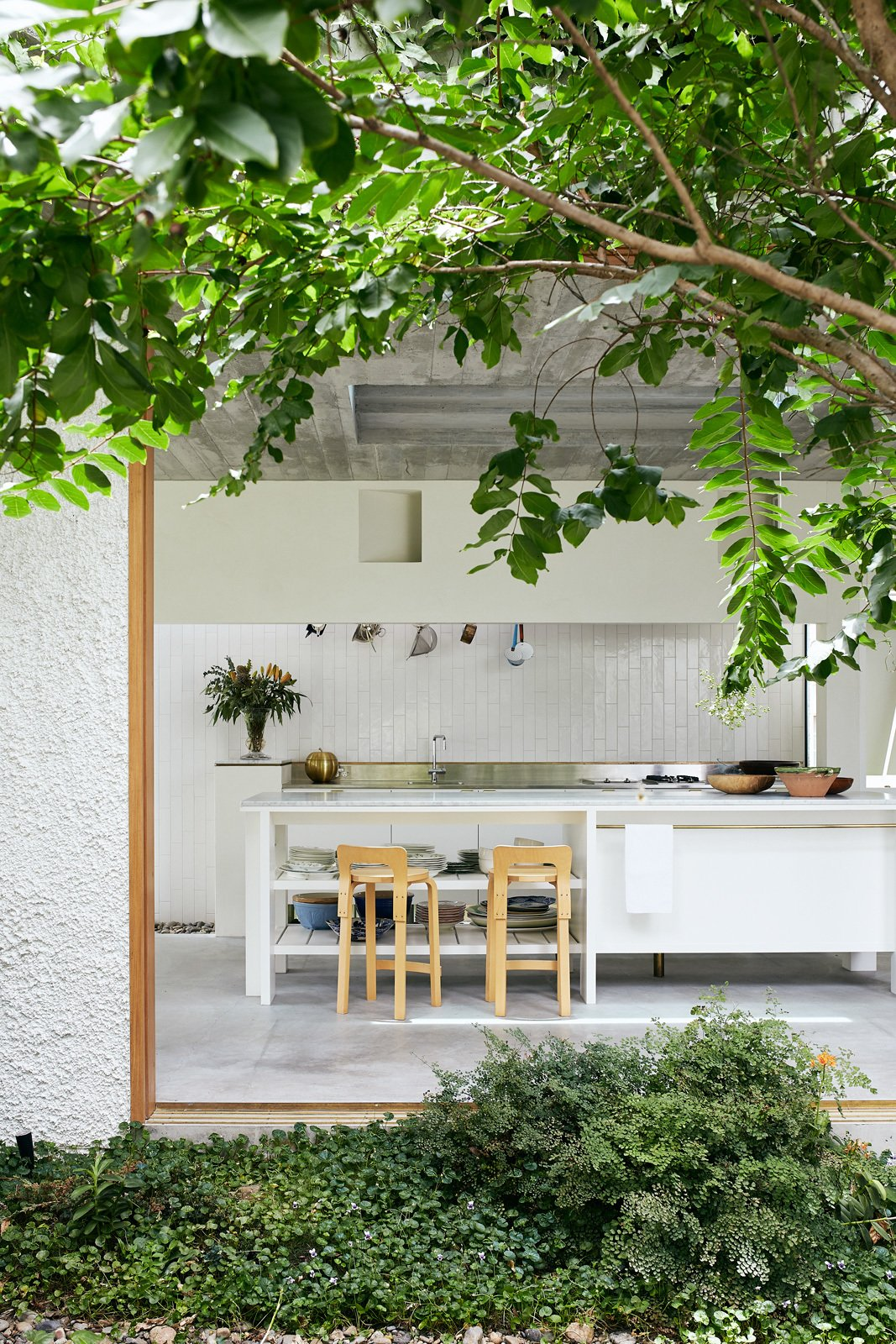 Kitchen, White, Subway Tile, Concrete, Drop In, Cooktops, and Marble The open kitchen has a warm Mediterranean-like feel and overlooks the central garden.    Best Kitchen Concrete Photos from An Australian Cottage Gets a Mediterranean-Inspired Revamp