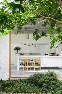 "When tapped to redesign a darling cottage in Brisbane's Little Italy, the team at Cavill Architects was inspired by ""architecture with veneration for the past."" As a result, the newly remodeled dwelling now pays homage to the Italian migrant workers' housing that was a crucial part of the Australian city's post-war settlement. The open kitchen has a warm Mediterranean-like feel and overlooks the central garden."
