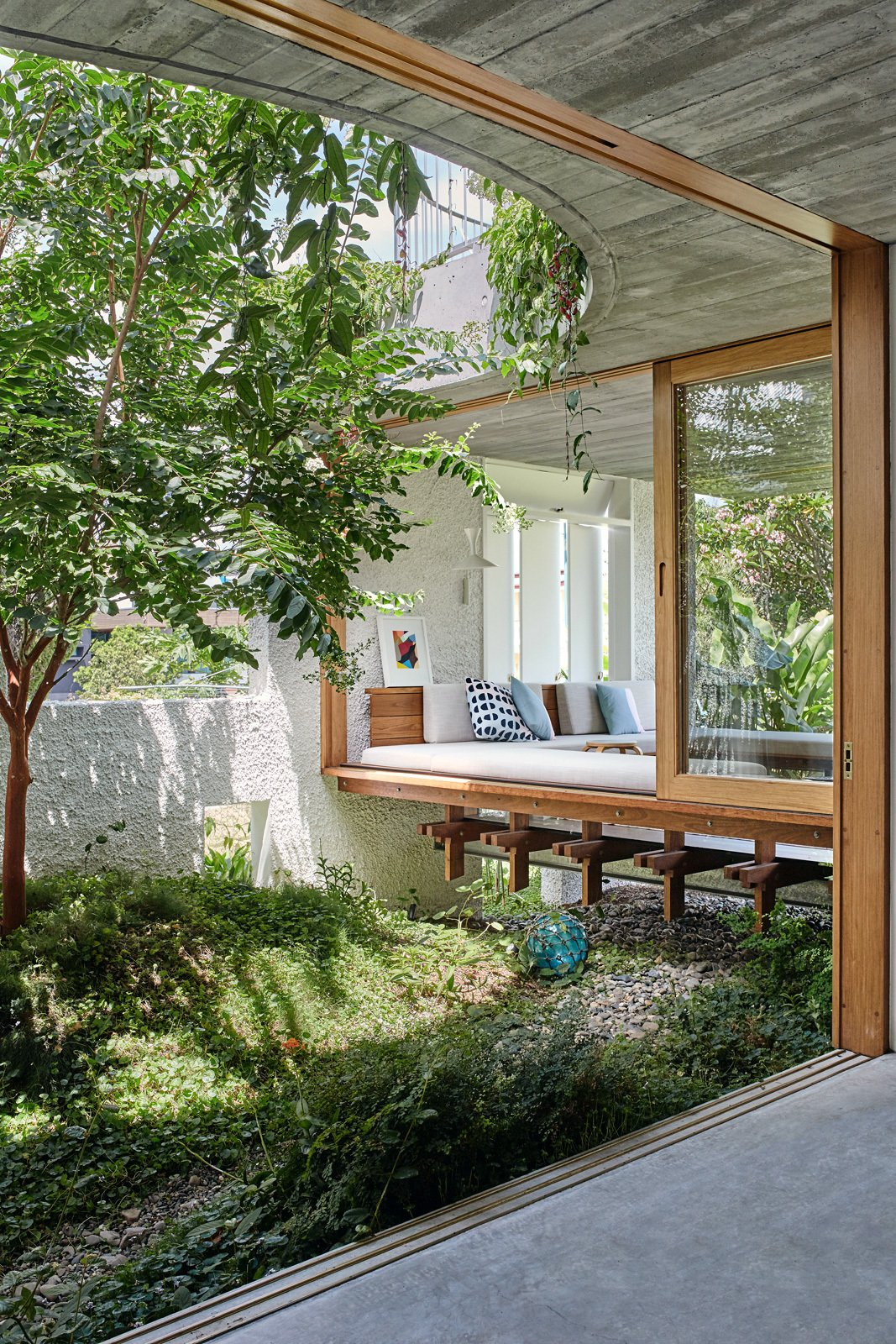 Living Room, Bench, Sofa, and Concrete Floor Large sliding doors fully enable indoor/outdoor living.  Best Photos from An Australian Cottage Gets a Mediterranean-Inspired Revamp